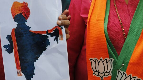 A participant displays an artist's impression of the India map decorated with a saffron shawl as ruling Bharatiya Janata Party (BJP) supporters celebrate government revoking disputed Kashmir's special status in Prayagraj, India, Monday, Aug. 5, 2019. - Sputnik International