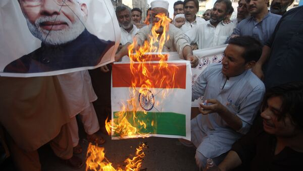 Pakistanis burn a representation of an Indian flag and a poster of Indian Prime Minster Narendra Modi during a protest to express support and solidarity with Indian Kashmiri people in their peaceful struggle for their right to self-determination, in Peshawar, Pakistan, Monday, Aug. 5, 2019 - Sputnik International