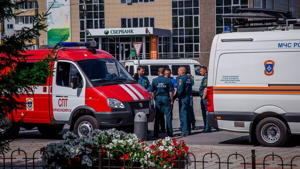Russian Emergency Situation Ministry officers wait near their cars in the town of Achinsk, some 150 km west of Krasnoyarsk, Russia. The fire hit ammunition depot at a military base outside the town on August 5 leaving leaving 12 people injured - Sputnik International