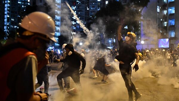 Protesters throw back tear gas fired by the police in Wong Tai Sin during a general strike in Hong Kong on August 5, 2019, as simultaneous rallies were held across seven districts. - Sputnik International