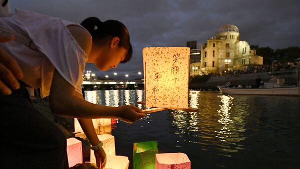 Girl releases paper lanterns on the Motoyasu River facing the gutted Atomic Bomb Dome in Hiroshima - Sputnik International