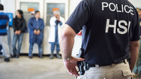 Homeland Security Investigations (HSI) officers from Immigration and Customs Enforcement (ICE) look on after executing search warrants and making some arrests at an agricultural processing facility in Canton - Sputnik International