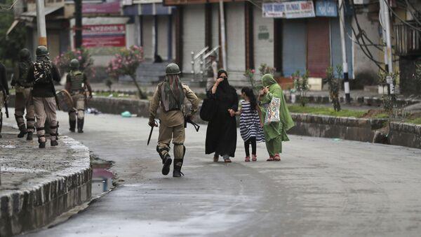Kashmiris walks past Indian paramilitary soldiers patrolling a street in Srinagar, Indian controlled Kashmir, Saturday, Aug. 10, 2019 - Sputnik International