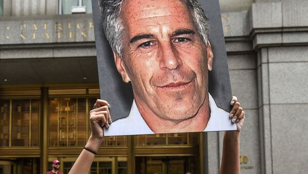 (FILES) In this file photo taken on July 8, 2019, a protest group called Hot Mess hold up photos of Jeffrey Epstein in front of the Federal courthouse on July 8, 2019 in New York City - Sputnik International