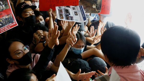 Anti-government protesters try to prevent a passenger from breaching a barricade in front of departure gates, during a demonstration at Hong Kong Airport, China August 13, 2019. - Sputnik International