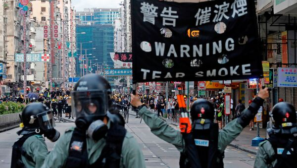 A riot police raises a warning flag as they try to disperse anti-extradition bill protesters by tear gas at Sham Shui Po in Hong Kong, China August 11, 2019. REUTERS/Tyrone Siu - Sputnik International