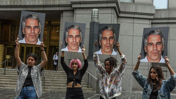 In this file photo taken on July 8, 2019, a protest group called Hot Mess hold up photos of Jeffrey Epstein in front of the Federal courthouse on July 8, 2019 in New York City. - Sputnik International