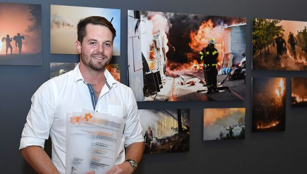 South Africa's Justin Sullivan poses for a photo with his work in the background after receiving 1st place in Top News, Single nomination and 2nd place in My Planet, Series nomination at the Andrey Stenin International Press Photo Contest Exhibition, in Moscow, Russia, November 8, 2018. The Andrei Stenin International Photo Contest is an annual contest for young photojournalists aged between 18 and 33 years old. - Sputnik International