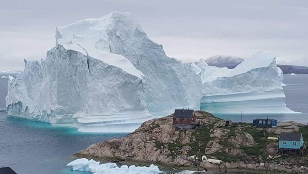 A picture taken on July 13, 2018 shows an iceberg behind houses and buildings after it grounded outside the village of Innarsuit, an island settlement in the Avannaata municipality in northwestern Greenland. - Sputnik International