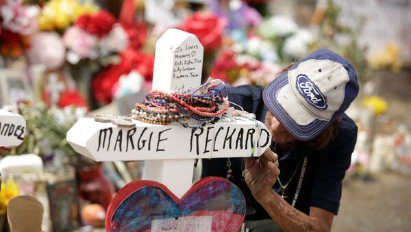 Antonio Basco, whose wife Margie Reckard was murdered during a shooting at a Walmart store, touches a white wooden cross bearing the name of his late wife, at a memorial for the victims of the shooting in El Paso, Texas, U.S. - Sputnik International