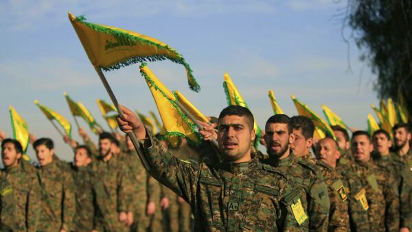 Hezbollah fighters hold flags as they attend the memorial of their slain leader Sheik Abbas al-Mousawi, who was killed by an Israeli airstrike in 1992 - Sputnik International