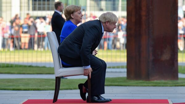 German Chancellor Angela Merkel and British Prime Minister Boris Johnson sit for the national anthems during a ceremony with military honours at the Chancellery on his first foreign visit since taking office on August 21, 2019 in Berlin - Sputnik International