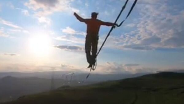 A professional slackliner Friedrich Kühne from Germany has filmed stunning mid-air 1050 feet (320 meters) walk between two power transmission towers in Armenia during 70 mph winds - Sputnik International