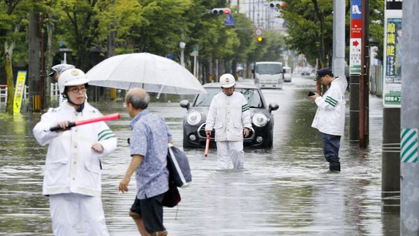 Police officers check a submerged street at a flooded area in Saga, Saga prefecture, southern Japan August 28, 2019, in this photo taken by Kyodo. - Sputnik International