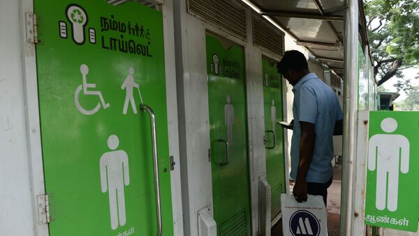 An Indian resident checks his phone as he waits to use a public toilet on a street in  Chennai on November 15, 2017 - Sputnik International