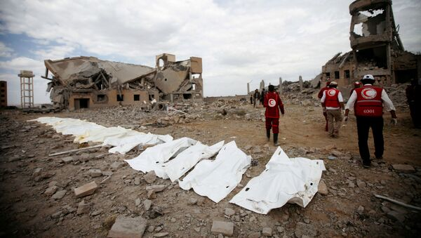 Red Crescent medics walk next to bags containing the bodies of victims of Saudi-led airstrikes on a Houthi detention centre in Dhamar - Sputnik International