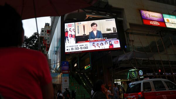 People watch a news conference of Hong Kong's Chief Executive Carrie Lam televised on a big screen in a shopping mall in Hong Kong - Sputnik International