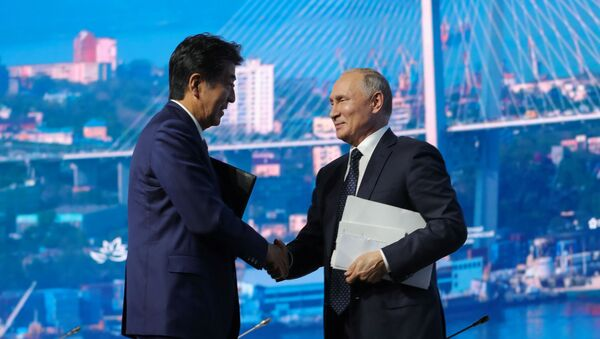 Russian President Vladimir Putin shakes hands with Japanese Prime Minister Shinzo Abe after a plenary session of the Eastern Economic Forum in Vladivostok, Russia September 5, 2019 - Sputnik International
