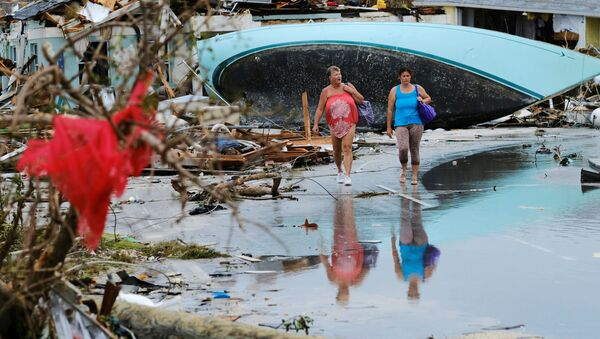 Women walk through the rubble in the aftermath of Hurricane Dorian on the Great Abaco island town of Marsh Harbour, Bahamas, September 3, 2019.  - Sputnik International