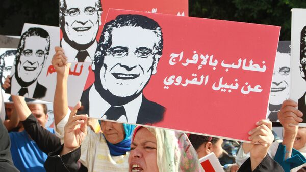 Supporters of presidential candidate Nabil Karoui carry placards with his image and slogans in his favour as they rally in front of the tribunal in the Tunisian capital Tunis asking for his release from prison on September 3, 2019. - Sputnik International