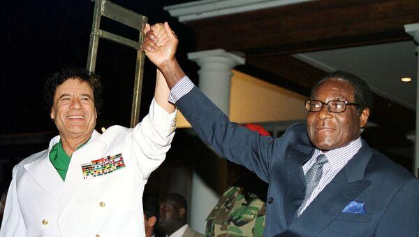 Libyan leader Colonel Muammar Gaddafi (L) and Zimbabwe President Robert Mugabe greet supporters outside State House in Harare, Zimbabwe July 12, 2001 - Sputnik International