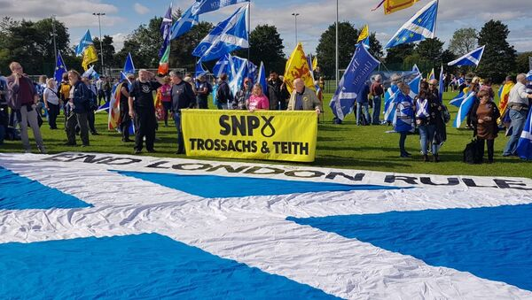March for Scottish Independence: An SNP branch banner hovers over a large saltire with 'End London Rule' inscribed above - Sputnik International