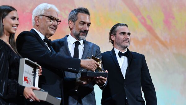 US director Todd Phillips (C), flanked by US actor Joaquin Phoenix (R) and President of the Venice Biennale Paolo Baratta, holds the Golden Lion award for Best Film he received for the movie Joker during the awards ceremony of the 76th Venice Film Festival on September 7, 2019 at Venice Lido.  - Sputnik International