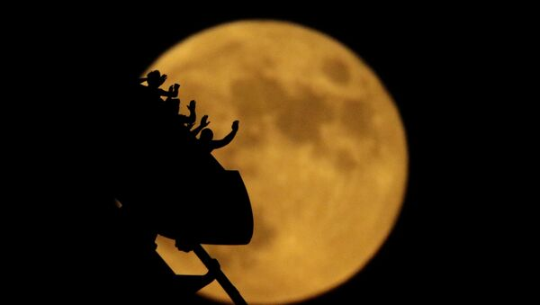 The full moon rises silhouetting roller coaster riders at the Worlds of Fun amusement park on the 50th anniversary of the Apollo 11 moon launch Tuesday, July 16, 2019, in Kansas City, Mo - Sputnik International