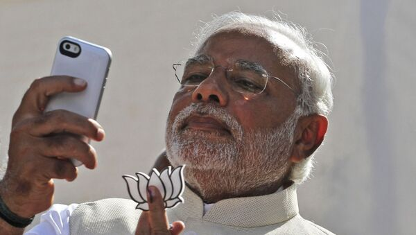 FILE- In this April 30, 2014 file photo, India's main opposition Bharatiya Janata Party's prime ministerial candidate Narendra Modi holds his party's symbol and looks into his phone after casting his vote in Ahmadabad, India - Sputnik International