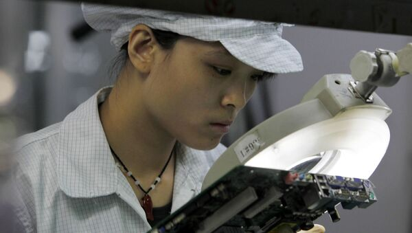 A staff member works on the production line at the Foxconn complex in the southern Chinese city of Shenzhen, Southern city in China, Wednesday, May 26, 2010 - Sputnik International
