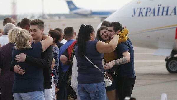 Relatives of Ukrainian prisoners freed by Russia greet them upon their arrival at Boryspil airport, outside Kyiv, Ukraine, Saturday, Sept. 7, 2019. Planes carrying prisoners freed by Russia and Ukraine have landed in the countries' capitals, in an exchange that could be a significant step toward improving relations between Moscow and Kyiv. The planes, each reportedly carrying 35 prisoners, landed almost simultaneously at Vnukovo airport in Moscow and at Kyiv's Boryspil airport. (AP Photo/Efrem Lukatsky) - Sputnik International