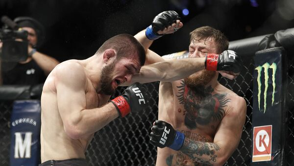 Khabib Nurmagomedov, left, and Conor McGregor throw punches during a lightweight title mixed martial arts bout at UFC 229 in Las Vegas, Saturday, Oct. 6, 2018 - Sputnik International