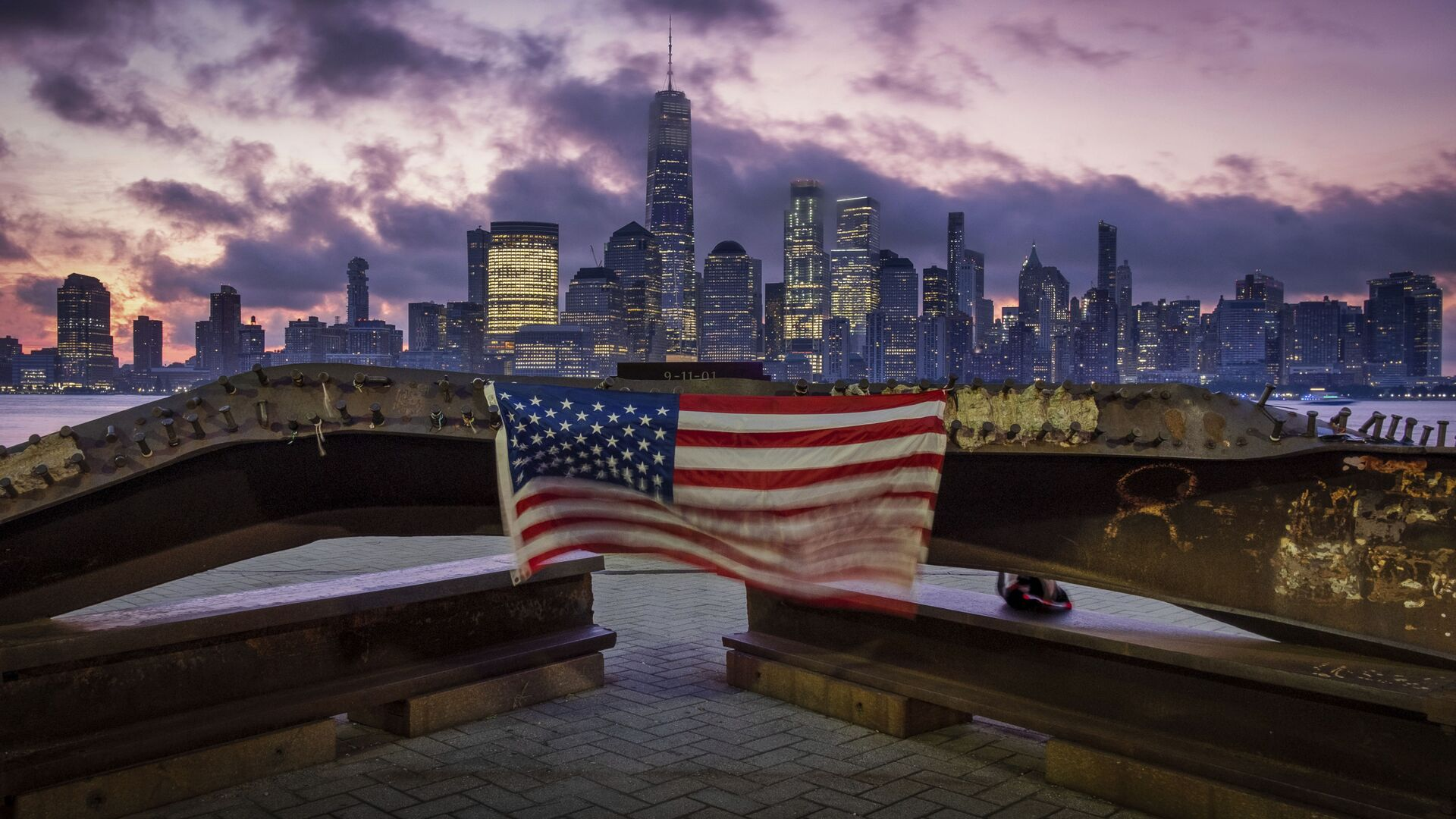 A US flag hanging from a steel girder, damaged in the 11 September 2001 attacks on the World Trade Center, blows in the breeze at a memorial in Jersey City, New Jersey on 11 September 2019. - Sputnik International, 1920, 06.09.2021