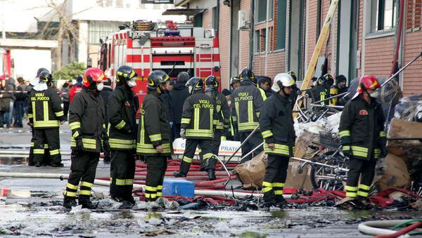 Firefighters inspect the area where a fire broke out in a Chinese-run garment factory in Prato, near Florence, Italy, Sunday, Dec. 1, 2013 - Sputnik International