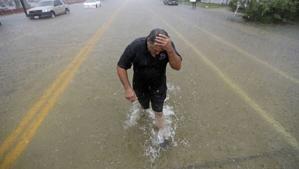 Angel Marshman wades through floodwaters from Tropical Depression Imelda after trying to start his flooded car Wednesday, Sept. 18, 2019, in Galveston, Texas. (AP Photo/David J. Phillip) - Sputnik International