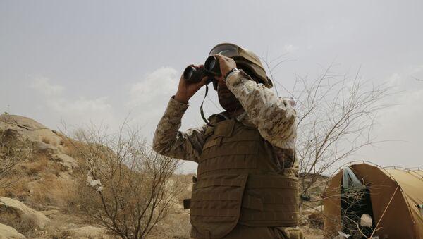 A Saudi soldier looks with binoculars toward the border with Yemen in Jazan, Saudi Arabia, Monday, April 20, 2015 - Sputnik International