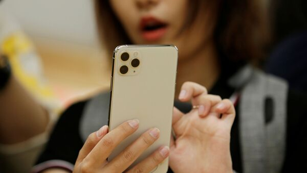 A woman holds an iPhone 11 Pro Max while giving a live broadcast after it went on sale at the Apple Store in Beijing, China, September 20, 2019 - Sputnik International