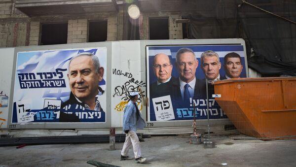 A man walks by election campaign billboards showing Benjamin Netanyahu, left, alongside the Blue and White party leaders - Sputnik International