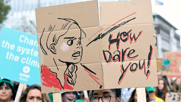 A participant holds a drawing depicting Swedish environmental activist Greta Thunberg during a protest march to call for action against climate change, in The Hague, Netherlands September 27, 2019 - Sputnik International