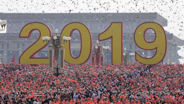 Doves are released over people holding Chinese flags at the end of the parade marking the 70th founding anniversary of People's Republic of China, on its National Day in Beijing, China October 1, 2019 - Sputnik International