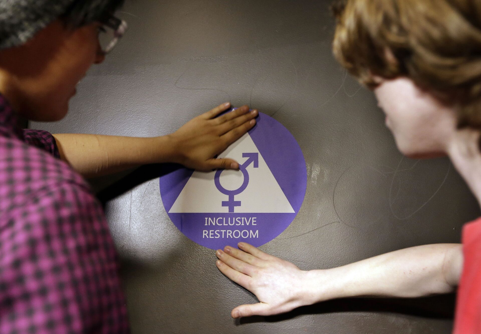 Destin Cramer, left, and Noah Rice place a new sticker on the door at the ceremonial opening of a gender neutral bathroom at Nathan Hale high school Tuesday, May 17, 2016, in Seattle - Sputnik International, 1920, 18.09.2021