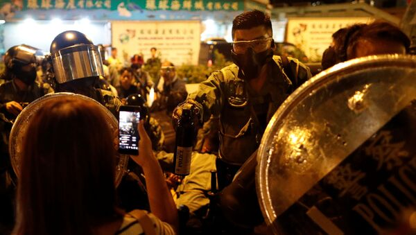 A police officer holds a bottle of peper spray against protesters at a demonstration at Taikoo station in Hong Kong, China October 3, 2019 - Sputnik International