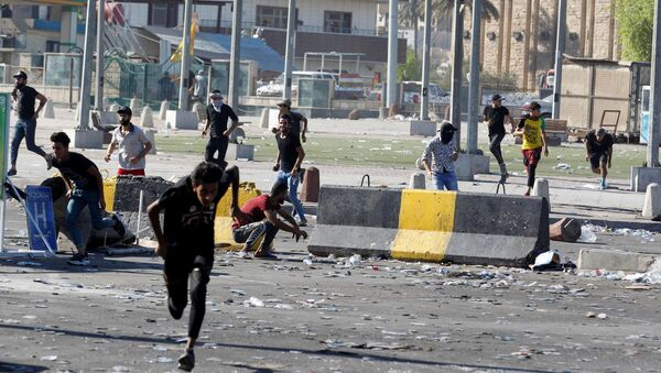 Demonstrators run at a protest during a curfew, three days after the nationwide anti-government protests turned violent, in Baghdad, Iraq October 4, 2019 - Sputnik International
