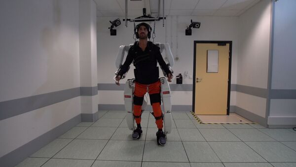A patient with tetraplegia walks using an exoskeleton in Grenoble, France, in February 2019 - Sputnik International