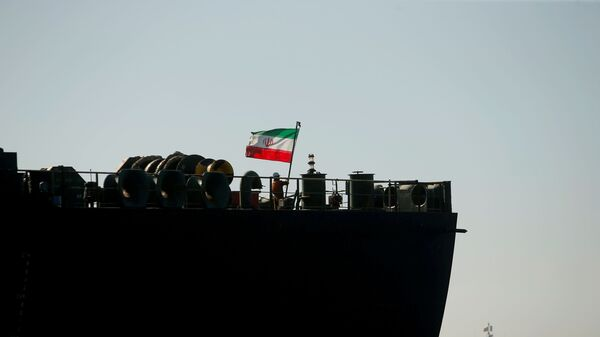 A crew member raises the Iranian flag at Iranian oil tanker Adrian Darya 1, formerly named Grace 1, as it sits anchored after the Supreme Court of the British territory lifted its detention order, in the Strait of Gibraltar, Spain, August 18, 2019. - Sputnik International