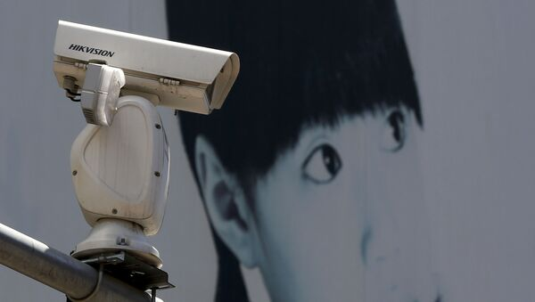 A video surveillance camera made by China's Hikvision is mounted on top of a street near a advertisement poster in Beijing. - Sputnik International
