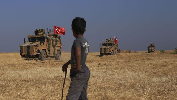 A Turkish n armored vehicles patrol as they conduct a joint ground patrol with American forces in the so-called safe zone on the Syrian side of the border with Turkey, near the town of Tal Abyad, northeastern Syria, Friday, Oct.4, 2019 - Sputnik International