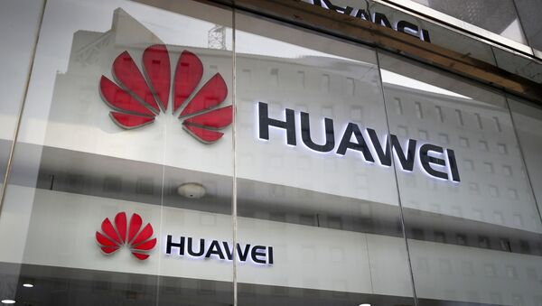 FILE - In this Jan. 29, 2019, file photo, the logos of Huawei are displayed at its retail shop window reflecting the Ministry of Foreign Affairs office in Beijing - Sputnik International