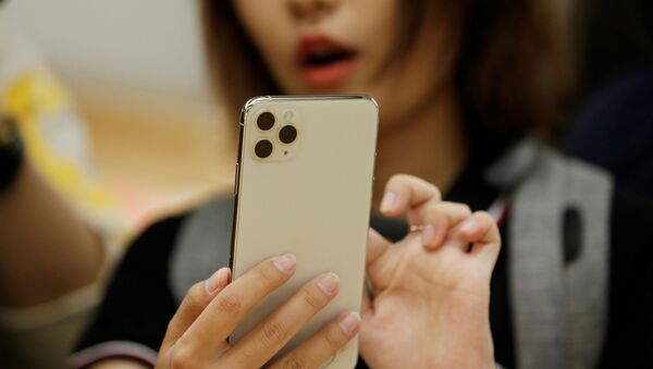 A woman holds an iPhone 11 Pro Max after it went on sale at the Apple Store in Beijing - Sputnik International