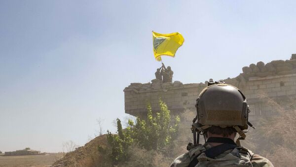 In this Sept. 21, 2019, photo, released by the U.S. Army, a U.S. soldier oversees members of the Syrian Democratic Forces as they demolish a Kurdish fighters' fortification and raise a Tal Abyad Military Council flag over the outpost as part of the so-called safe zone near the Turkish border. - Sputnik International